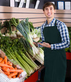Grocery worker selling vegetables Stock Photo