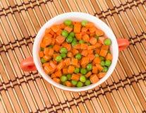 Grochy i marchewki w talerzu Obraz Royalty Free