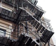 Grodaperspektiv på den stora gamla byggnaden med metalltrappa Byggnad som göras av tegelstenar Metallkonstruktion på byggnaden Br arkivbilder