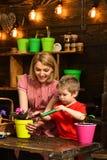 Groddbegrepp Moder och litet barn som transplanterar houseplantgrodden Modern och sonen replant blommagrodden i ny kruka arkivfoton