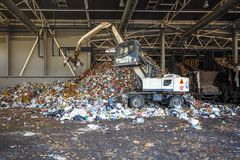 GRODNO, БЕЛАРУСЬ - МАЙ 2018: Экскаватор на основной сортировать отброса на ненужном заводе по обработке Отдельно сбор мусора стоковые фотографии rf