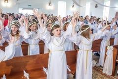GRODNO, БЕЛАРУСЬ - МАЙ 2019: Маленькие ребята в католической церкви ждут первую общность евхаристии Немногое ангелы внутри стоковое изображение rf
