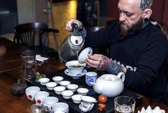 GRODNO, БЕЛАРУСЬ - 17-ОЕ АПРЕЛЯ: Бородатый человек участвует в церемонии чая, 17-ое апреля 2016 GRODNO, БЕЛАРУСИ Стоковое фото RF