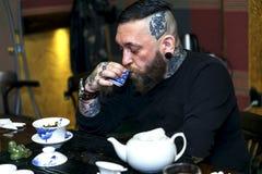 GRODNO, БЕЛАРУСЬ - 17-ОЕ АПРЕЛЯ: Бородатый человек участвует в церемонии чая, 17-ое апреля 2016 GRODNO, БЕЛАРУСИ Стоковая Фотография