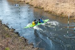 GRODNO, BELARUS - APRIL, 2019: kayak freestyle competition on fast cold water river strenuously rowing, spirit of victory stock images