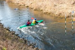 GRODNO, BELARUS - APRIL, 2019: kayak freestyle competition on fast cold water river strenuously rowing, spirit of victory stock photo