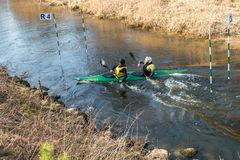 GRODNO, BELARUS - APRIL, 2019: kayak freestyle competition on fast cold water river strenuously rowing, spirit of victory stock image