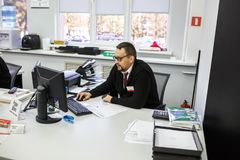 GRODNO, BELARUS - AUGUST 2017: employees to answer the call in the store at work at the computer in modern shop stock photo