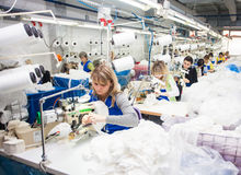 GRODNO, BELARUS - DECEMBER 13, 2013: Seamstress in textile factory sewing with a industrial sewing machine Stock Images