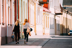 Grodno, Belarus Duas jovens mulheres que andam perto das fachadas de construções de casas tradicionais velhas em Sunny Summer Day Imagem de Stock Royalty Free