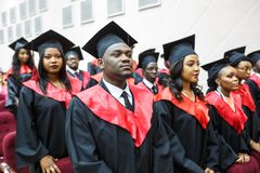 GRODNO, BELARUS - JUNE, 2018: Foreign african medical students in square academic graduation caps and black raincoats during stock photos
