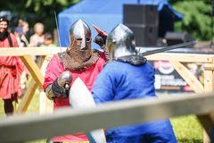 GRODNO, BELARUS - JUNE 2019: medieval jousting knight fight, in armor, helmets, chain mail with axes and swords on lists. historic stock image