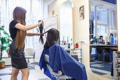 GRODNO, BELARUS - MAI 2016 : coiffeur principal de coiffeur faisant une coiffure dans le salon de coiffeur pour la jeune femme images libres de droits