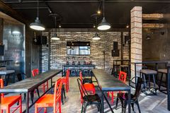 GRODNO, BELARUS - MARCH, 2019: inside interior in modern pub sport bar with dark loft design style with red chairs stock image