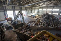 Excavator on primary sorting of garbage at waste processing plant. Separate garbage collection. royalty free stock images