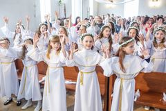GRODNO, BELARUS - MAY 2019: Young children in the Catholic Church are waiting for the first eucharist communion. Little angels in. White clothes stock photos