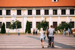 Grodno, Belarus Pares jovenes de la familia con un cochecito que camina cerca de la casa vieja del vicio - administrador In Sunny Foto de archivo