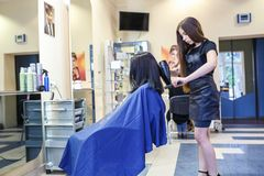 GRODNO BIAŁORUŚ, MAJ, - 2016: mistrzowski fryzjera coiffeur robi fryzurze w fryzjera męskiego salonie dla młodej kobiety zdjęcie stock
