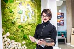GRODNO, BIELORRÚSSIA - EM MARÇO DE 2019: empregados de jovem mulher nos trabalhos de vidro no computador na loja moderna imagem de stock