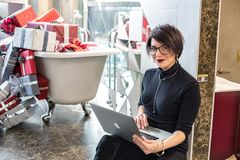 GRODNO, BIELORRÚSSIA - EM MARÇO DE 2019: empregados de jovem mulher nos trabalhos de vidro no computador na loja moderna com banh imagens de stock royalty free