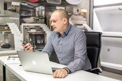 GRODNO, BIELORRÚSSIA - EM MARÇO DE 2019: trabalhos dos empregados do homem novo no computador na loja sondando luxuosa moderna fotos de stock royalty free