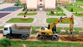 GRODNO, BIELORRÚSSIA - EM SETEMBRO DE 2018: A máquina escavadora escava um poço e carrega a areia em um caminhão basculante filme