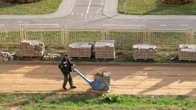 Grodno, Bielorrusia - octubre de 2018: El trabajador alisa la arena antes de poner las losas almacen de video