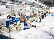 GRODNO, BIELORUSSIA - 13 DICEMBRE 2013: Cucitrice nella fabbrica del tessuto che cuce con una macchina da cucire industriale Immagini Stock