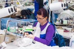 GRODNO, BIELORUSSIA - 13 DICEMBRE 2013: Cucitrice nella fabbrica del tessuto che cuce con una macchina da cucire industriale Immagine Stock Libera da Diritti