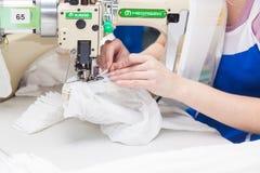 GRODNO, BIELORUSSIA - 13 DICEMBRE 2013: Cucitrice nella fabbrica del tessuto che cuce con una macchina da cucire industriale Immagini Stock Libere da Diritti