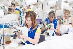GRODNO, BIELORUSSIA - 13 DICEMBRE 2013: Cucitrice nella fabbrica del tessuto che cuce con una macchina da cucire industriale fotografia stock