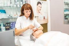 GRODNO, BIELORUSSIA - MAGGIO 2018: donna che fa massaggio facciale al salone di bellezza fotografie stock