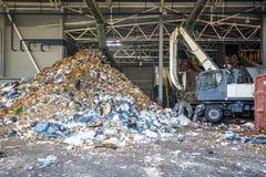 GRODNO, BIELORUSSIA - MAGGIO 2018: Escavatore sulla separazione primaria dell'immondizia nella pianta di trattamento dei rifiuti  immagini stock