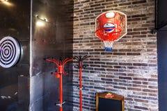 GRODNO, BIELORUSSIA - MARZO 2019: cerchio di pallacanestro dentro l'interno nella barra di sport moderna del pub con stile scuro  fotografia stock libera da diritti