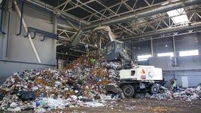 Grodno, Bielorussia - ottobre 2018: Escavatore sulla separazione primaria dell'immondizia nella pianta di trattamento dei rifiuti stock footage