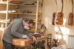 GRODNO VITRYSSLAND - JANUARI 18, 2017 Allvarlig yrkesmässig gitarr-tillverkare som arbetar med den oavslutade gitarren på seminar Royaltyfri Foto