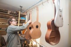 GRODNO VITRYSSLAND - JANUARI 18, 2017 Allvarlig yrkesmässig gitarr-tillverkare som arbetar med den oavslutade gitarren på seminar Fotografering för Bildbyråer