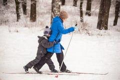 GRODNO VITRYSSLAND - JANUARI 15, 2017 Mamman undervisar sonen att skida i vinterskogen Arkivbild