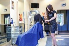 GRODNO VITRYSSLAND - MAJ 2016: ledar- frisörcoiffeur som gör en frisyr i barberaresalongen för ung kvinna arkivfoto