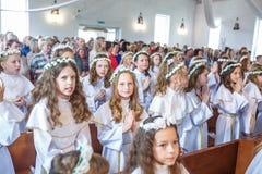 GRODNO VITRYSSLAND - MAJ 2019: Unga barn i katolska kyrkan v?ntar p? den f?rsta eucharistnattvardsg?ngen Sm? ?nglar in royaltyfria bilder