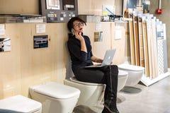 GRODNO VITRYSSLAND - MARS 2019: anställda för ung kvinna i exponeringsglasarbeten på datoren i modernt shoppar med badet av gåvor arkivbilder