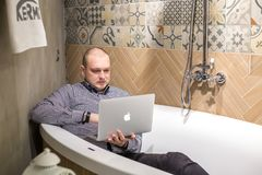 GRODNO VITRYSSLAND - MARS 2019: anställda för ung man lägger i bad med anteckningsbokdatoren i modernt lyxigt rörmokerilager royaltyfri fotografi