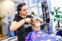 GRODNO, WEISSRUSSLAND - MAI 2016: Vorlagenfriseur Coiffeur, der eine Frisur im Friseursalon f?r kleinen Jungenjugendlichen tut stockfoto