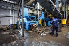 GRODNO, WEISSRUSSLAND - OKTOBER 2018: Arbeitskraft nahe Abfallpresse auf Verarbeitungsanlage der modernen Abfallaufbereitung Unte stockfoto