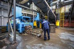 GRODNO, WEISSRUSSLAND - OKTOBER 2018: Arbeitskraft nahe Abfallpresse auf Verarbeitungsanlage der modernen Abfallaufbereitung Unte stockbild
