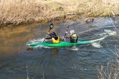 GRODNO, WIT-RUSLAND - APRIL, 2019: de concurrentie van het kajakvrije slag op snelle koud waterrivier die zwaar, geest van overwi stock afbeeldingen