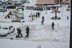 Grodno, Wit-Rusland, 12 15 2012 is Er heel wat sneeuw in de werf van het flatgebouw, het vriendschappelijke schoonmaken van de sn royalty-vrije stock foto