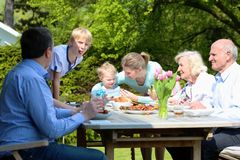 Große Familie, die im Garten zu Mittag isst Lizenzfreie Stockfotografie