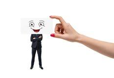 Große Frau ` s Hand setzt ein smileygesicht auf weiße Karikatur auf einem Angestellter ` s Kopf, der auf weißem Hintergrund lokal Lizenzfreie Stockfotos