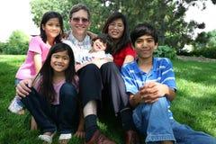 Große gemischtrassige Familie, die auf Rasen sitzt Stockbild